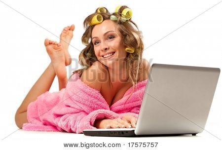 Young adult girl in pink dressing gown and with hair rollers lying with laptop