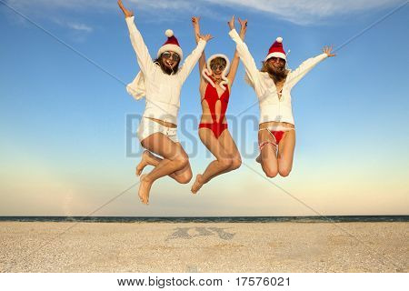 Three happy girls in Santa Clause suit having fun on the beach