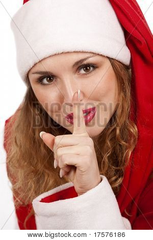 Santa girl  is putting her finger on lips and looking with a smile. Isolated on white.