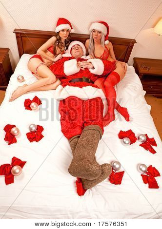 Portrait of Santa Claus sitting in the bed with two sexy girls in Santa hats