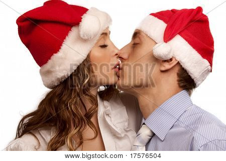 Portrait of Young kissing couple in Christmas hats. Isolated over white background