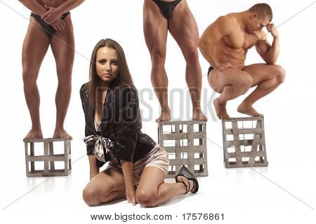 Beautiful young woman against three athletes, isolated on white
