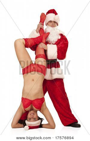 Portrait of Santa Claus holding female Santa in openwork red lingerie and stockings, which standing head first. Isolated on white.
