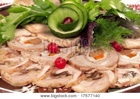 Big group of thinly sliced meat and cucumber in the form of rose