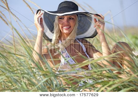 A beautiful blond haired blue eyed model wearing a white bikini and striped hat amid tall grass
