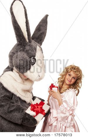 Portrait of big grey fur's color rabbit giving present to a pretty girl in pink dress against white background