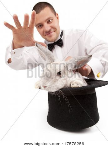 Man dressed as a magician conjuring with a rabbit in a top hat isolated over a white background