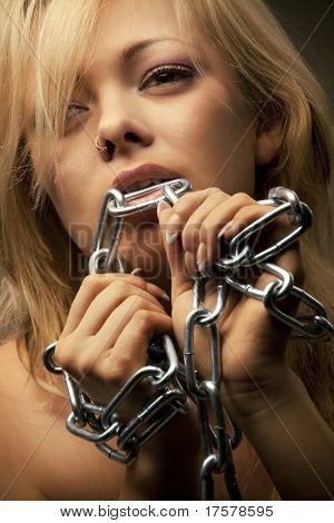 Shirtless sexy young caucasian woman biting a chrome chain over a dark background.