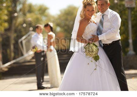 Feliz novia y el novio en la boda a pie abrazándose en el fondo de otros recién casados