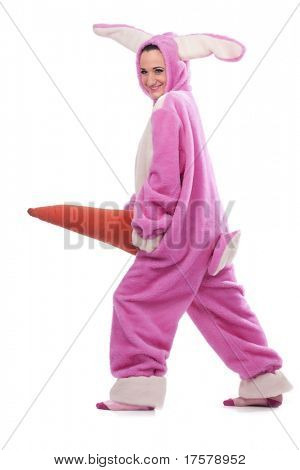 Funny pink rabbit with big carrot isolated on white background