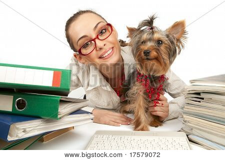 The young student girl with Yorkshire Terrier on table with papers isolated on a white background