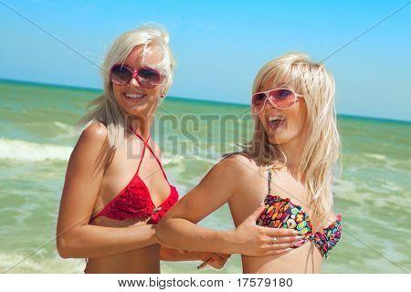 Pretty girl unfastening swimsuit of her girlfriend on the beach