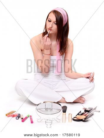 Teenage girl making make-up on a white background