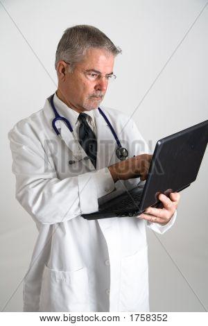 Docoter Working On Laptop Computer