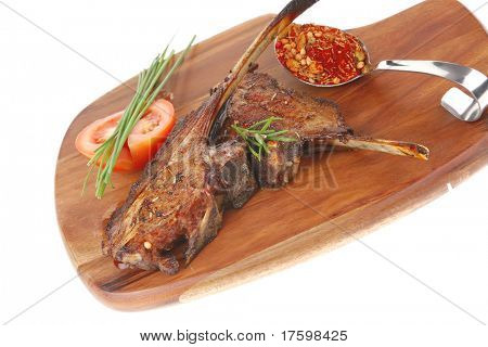 meat on wooden plate : roast ribs on wood with tomatoes chives and dry spices isolated on white background