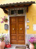 stock photo of wooden door  - a doorway in tuscany with flowers and wooden door - JPG