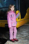 foto of night crawler  - Little girl in pink clothes standing on yellow crawler tractor in the dark - JPG
