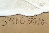 closeup of the text spring break written in the wet sand of the seashore, in a quiet beach poster