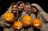 stock photo of nun  - Four smiling nuns in cassocks holding halloween pumpkins - JPG