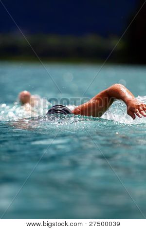 Crawling Young man swimming in a lake with professional gear on. Ideal shot for summer / vacation.