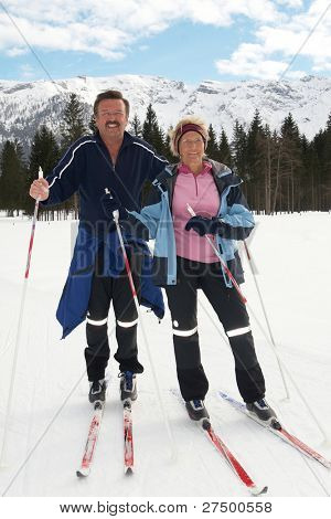 A senior couple outdoor in a winter setting. The active couple is about to go crosscountry skiing.
