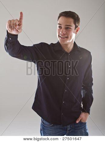 Young european male model is pushing a digital touchscreen buitton.