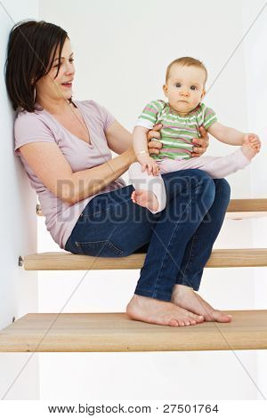 Young mother at home with her little baby on stairs.