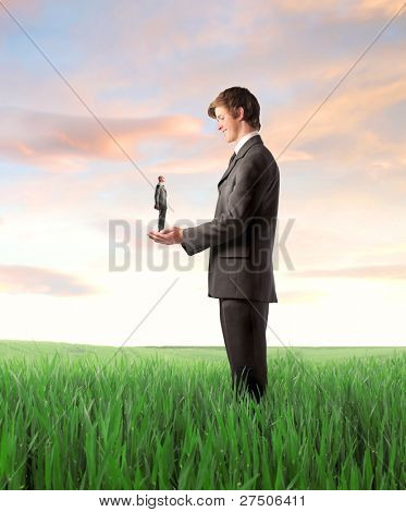 Smiling young businessman holding an older one on a green meadow