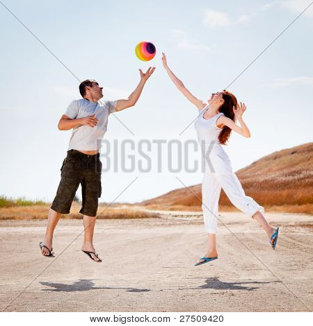 Happy couple jumping to catch a ball