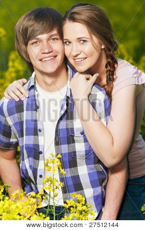Happy smiling young couple over yellow green rape meadow