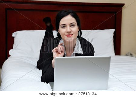 Portrait of young smiling business woman lying on bed with laptop in a hotel room