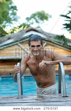 Portrait of smiling middle aged man standing in the pool
