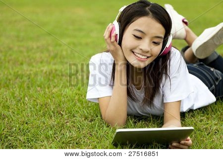 happy girl using tablet pc on the grass