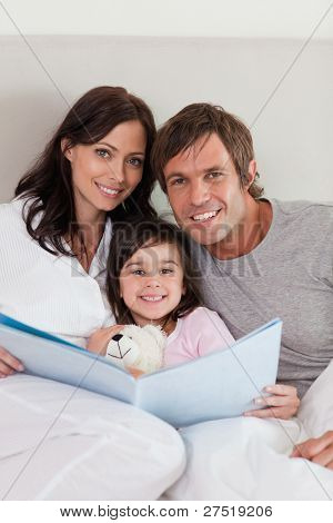 Portrait of parents reading a story to their daughter in a bedroom