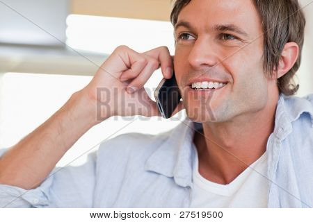 Close up of a smiling man making a phone call looking away from the camera