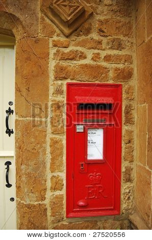 Red british post box on stone wall
