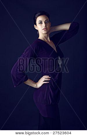 beautiful young brunette woman wearing purple mini dress on black studio background.