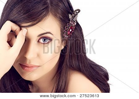 face of a beautiful young woman with brown long hair and pink eyeshadows and lipstick.