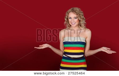 Smilng woman on red background with arms opened