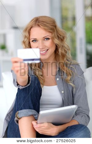 Blond woman doing online shopping with digital tablet