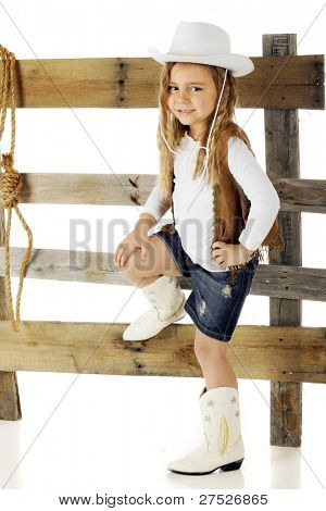 "An adorable kindergarten ""cowgirl"" hanging around an old rail fence.  On a white background."