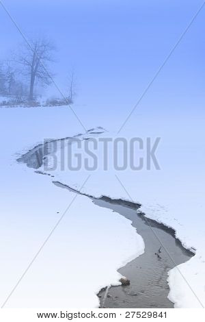 Stream flowing over a Frozen lake during Winter time