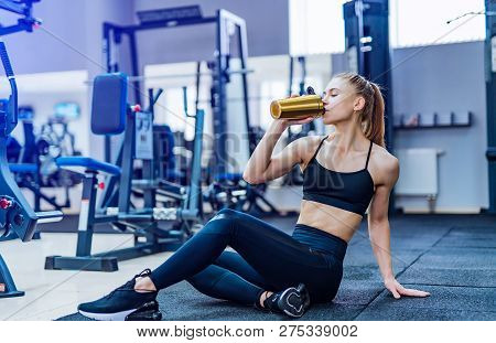 poster of Fitness Woman Drinking Water While Sitting And Resting On The Floor In Gym. Woman Exercise Workout I