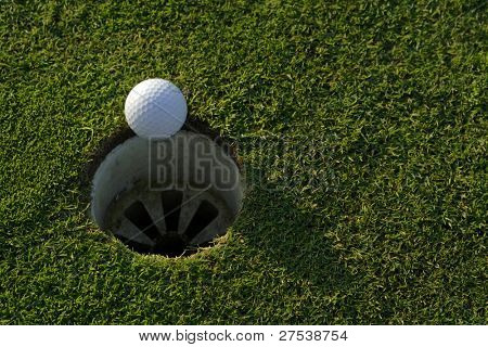 a golfball on the edge of the hole