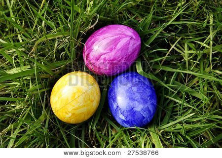 pink, yellow and blue eastereggs lying in the grass, birds view