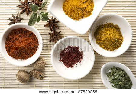 variety of spices and herbs - curry, sage, turmeric, cayenne pepper, nutmeg, saffron, star anise, dried ramsons decorated on straw mat
