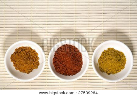 turmeric, cayenne pepper and curry in white bowls on straw placemat