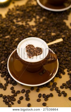 cup of cappuccino with heart shape on froth, coffeebeans around