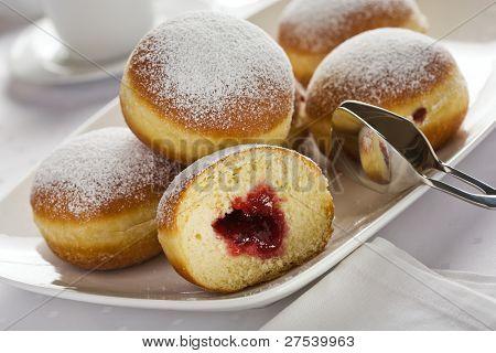 montón de mermelada lleno donuts de bismarck en la placa blanca