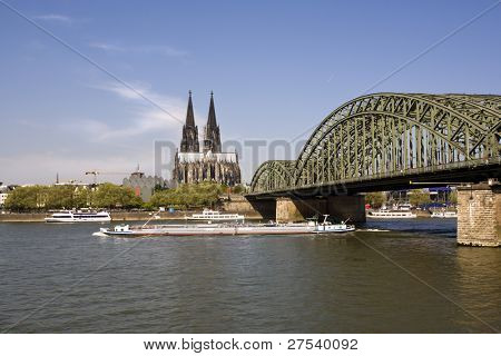 view along Hohenzollern bridge across the river Rhine to cologne cathedral, cargo ship passing by